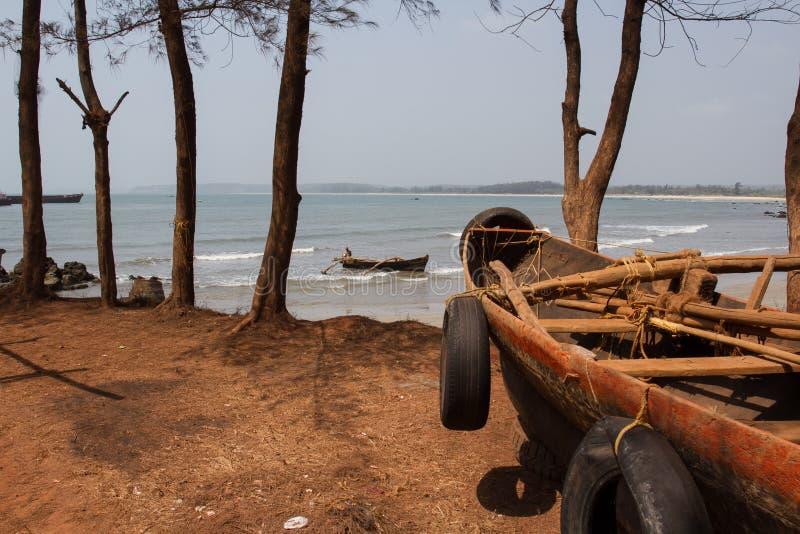 Un barco de pesca viejo en un bosque del pino en la orilla de un mar caliente imágenes de archivo libres de regalías