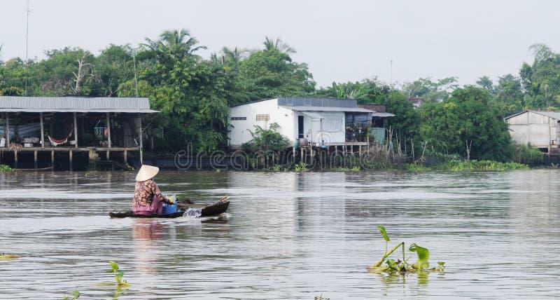 Un barco de rowing de la mujer en el río en Tien Giang, Vietnam fotos de archivo