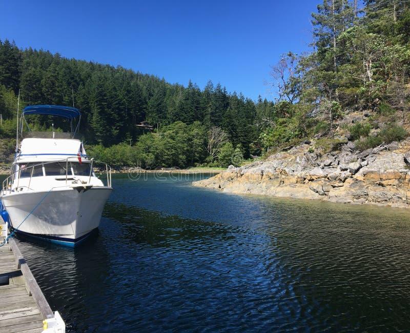 Un barco del poder atracado cerca de orilla en un día pacífico en la isla de Cortes, sonido de la desolación, Columbia Británica, fotos de archivo