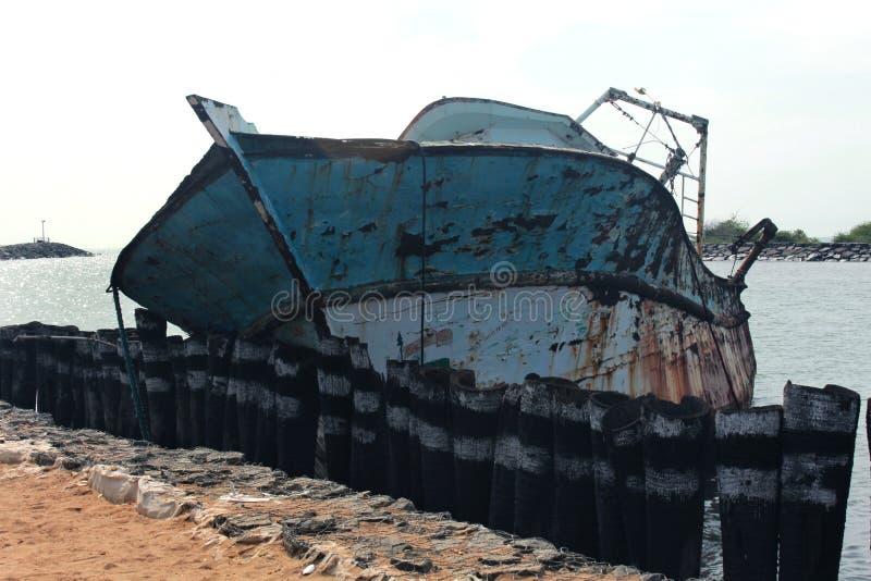 Un barco dilapidado del pescador en un pequeño puerto indio foto de archivo