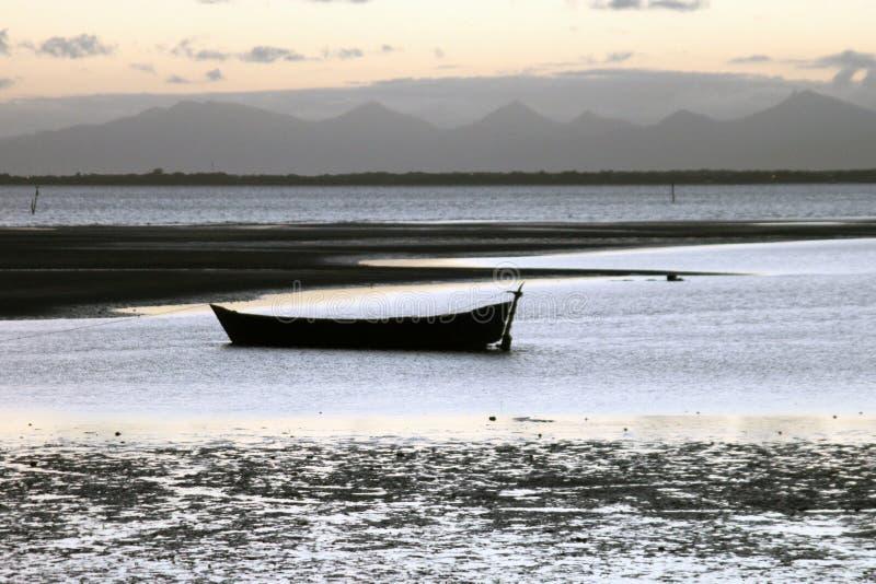 Un barco en la playa y los montains fotos de archivo