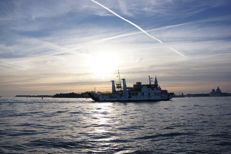 Un barco en la puesta del sol en Venecia fotografía de archivo