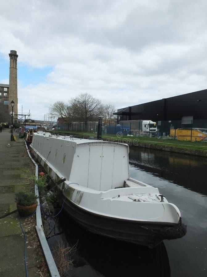 Un barco estrecho blanco amarró en el canal en un área industrial de Huddersfield con el molino y el puente foto de archivo