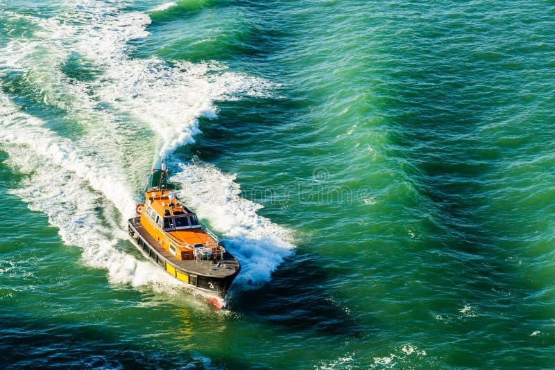 Un barco experimental que ayuda a un trazador de líneas de la travesía hacia fuera el puerto de Southampton en Inglaterra Septiem fotos de archivo libres de regalías