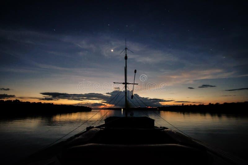 Un barco navega el río de Javari después de la puesta del sol imagenes de archivo