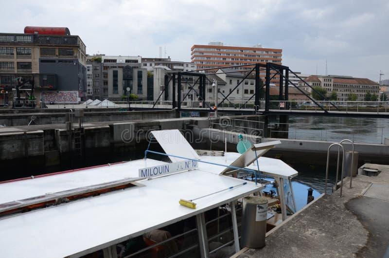 Un barco pasa una cerradura en el río Rhone en Ginebra imagenes de archivo
