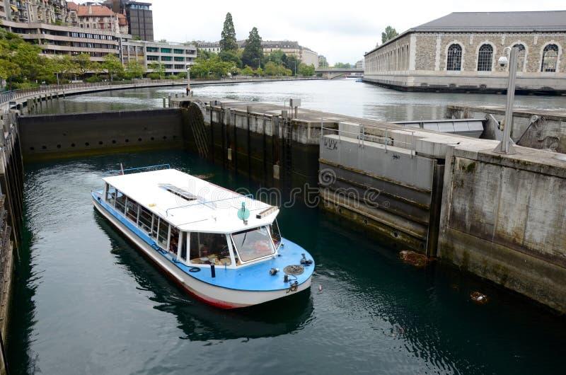 Un barco pasa una cerradura en el río Rhone en Ginebra foto de archivo libre de regalías