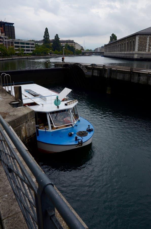 Un barco pasa una cerradura en el río Rhone en Ginebra fotos de archivo