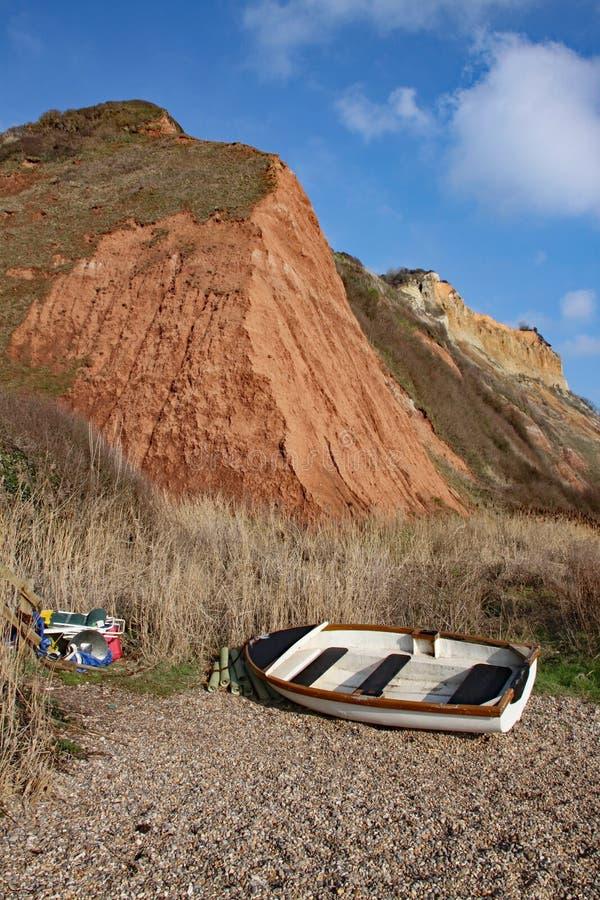 Un barco que rema y aparejos de pesca en la base de los acantilados de la piedra arenisca de la era jurásica que sube de la playa imagen de archivo libre de regalías