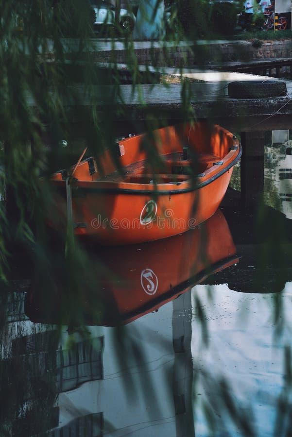 Un barco rojo amarrado en el lago foto de archivo