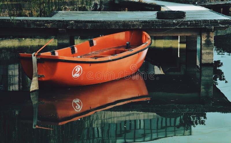 Un barco rojo amarrado en el lago fotografía de archivo