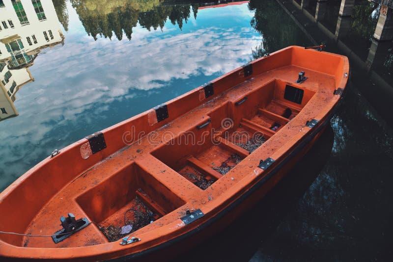 Un barco rojo amarrado en el lago imágenes de archivo libres de regalías