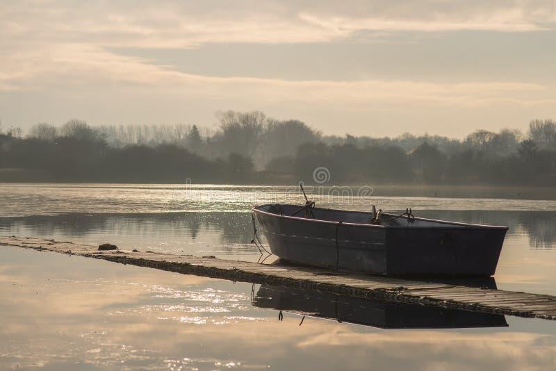 Un barco sin tripulación solitario sienta marcha lenta en un lago congelado durante salida del sol en Hornsea simple fotografía de archivo libre de regalías