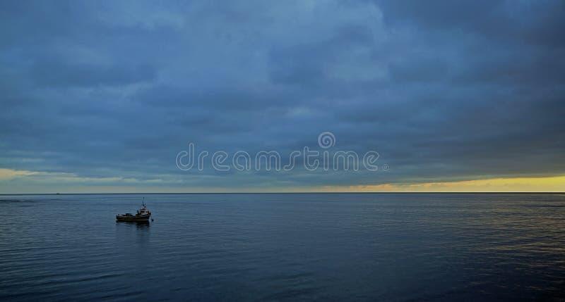 Un barco solitario se amarra en un mar plano en la salida del sol foto de archivo