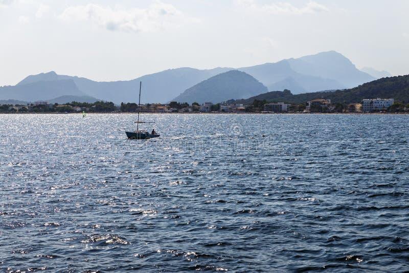 un barco solo con una vela bajada imagen de archivo libre de regalías