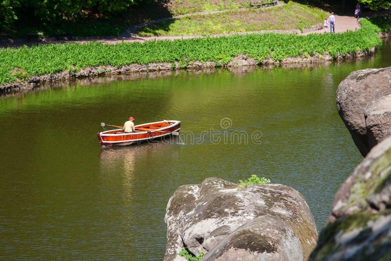 Un barco turístico en la superficie tranquila del lago en Sofiyivsky P fotografía de archivo