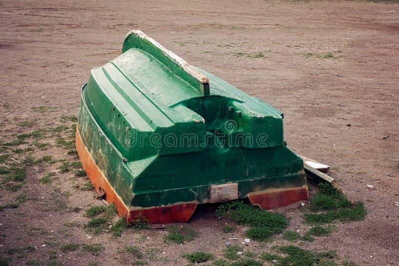 Un barco verde de la fibra de vidrio en la playa fotografía de archivo