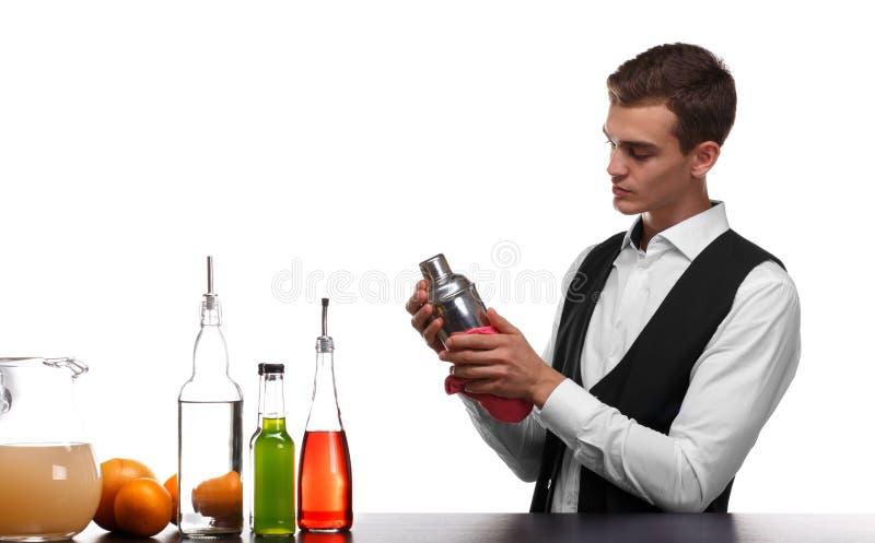 Un barkeeper que limpia una capacidad para los cócteles, aislada en un fondo blanco Camarero detrás de un contador de la barra co foto de archivo libre de regalías
