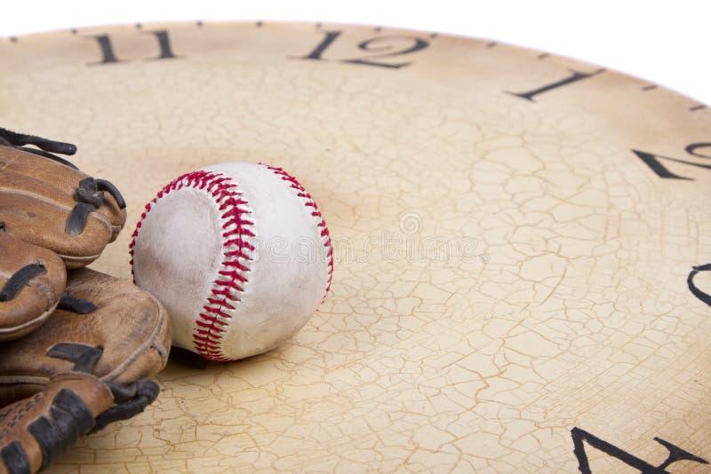Un base-ball et un gant sur un vieux cloc de vintage image libre de droits