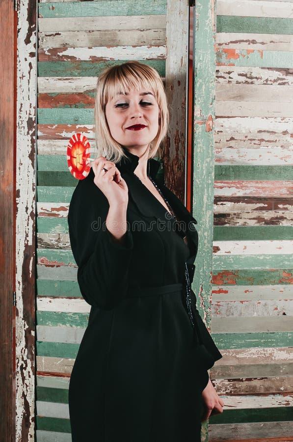 Un bastante rubio en el vestido negro que sostiene un palillo del caramelo rojo imágenes de archivo libres de regalías