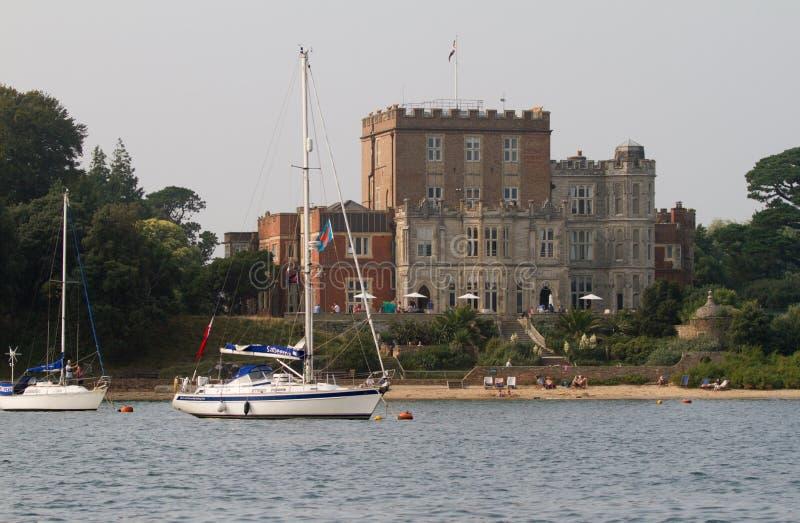 Un bateau a amarré vers le haut du château proche de brownsea dans le port de Poole image libre de droits