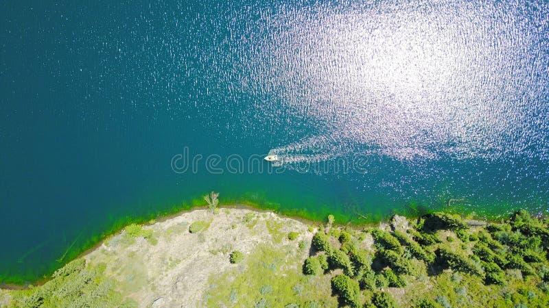 Un bateau au milieu d'un lac de montagne Lac de montagne de paysage dans la forêt photos libres de droits