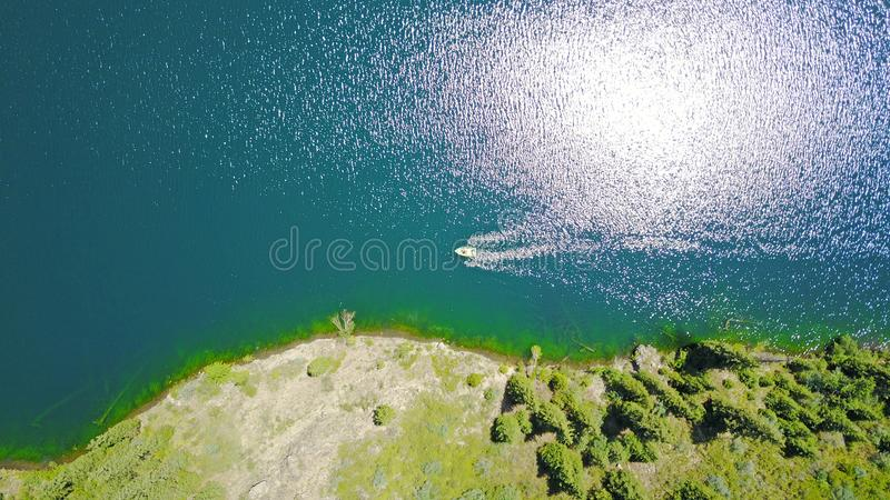 Un bateau au milieu d'un lac de montagne Lac de montagne de paysage dans la forêt image stock