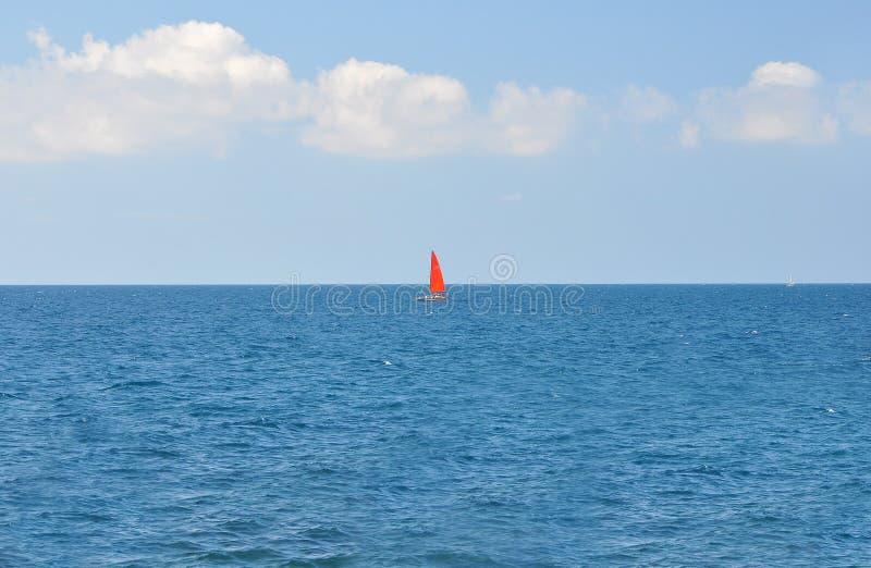 Un bateau avec une voile rouge flottant le long de la mer bleue sur un fond de ciel bleu images libres de droits