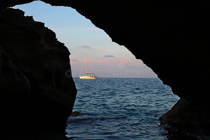 Un bateau dans des roches du ` s de Tropea photo stock