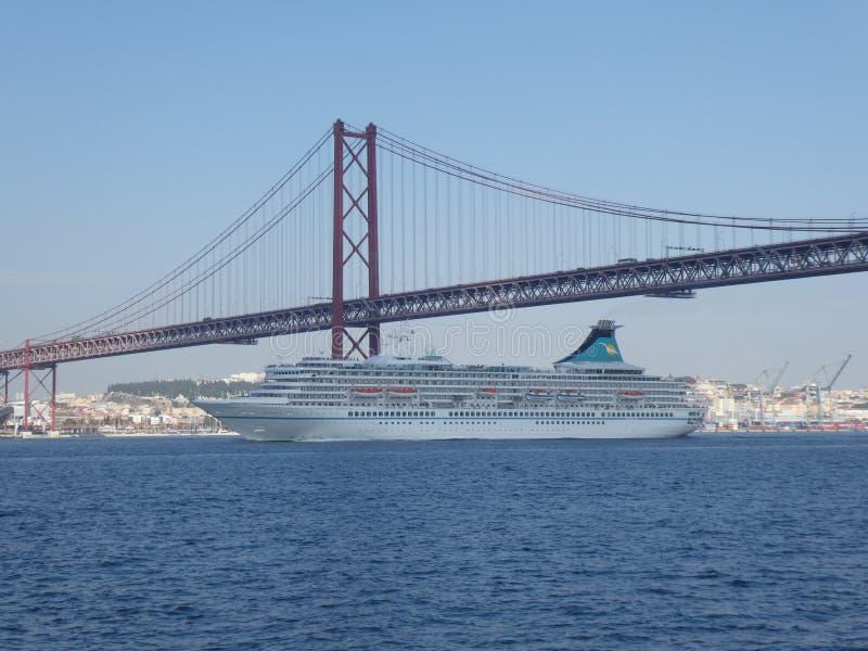 Un bateau de croisi?re navigue sous le pont du 25 avril ? Lisbonne, Portugal, l'Europe image stock