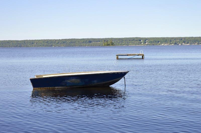 Un bateau de pêche isolé se repose ancré dans le frot d'un dock photo stock