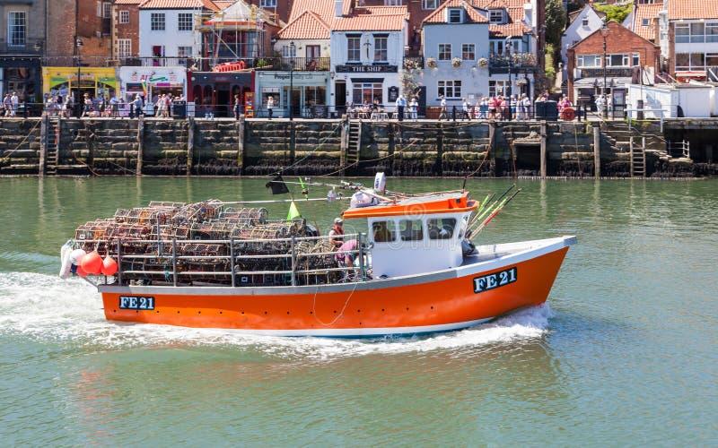Un bateau de pêche quitte la ville balnéaire de Whitby image libre de droits