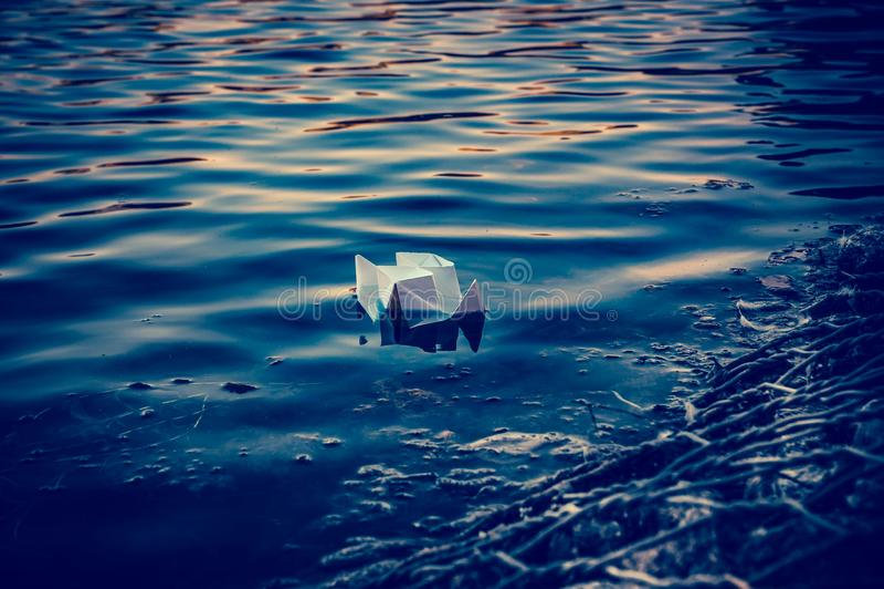 Un bateau de papier coulant dans l'eau foncée photo libre de droits