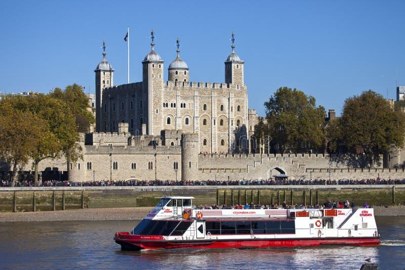 Un bateau de touristes passant la tour de Londres photos stock