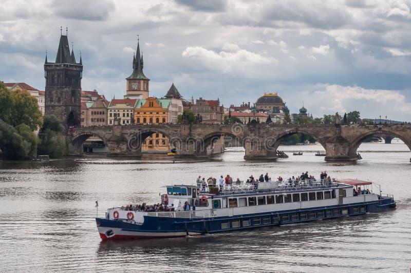 Un bateau de touristes sur le fond de Charles Bridge, Prague, République Tchèque image stock