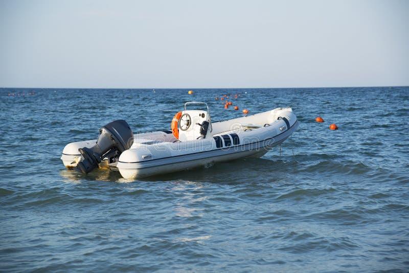 Un bateau gonflable avec un moteur en mer au coucher du soleil photographie stock