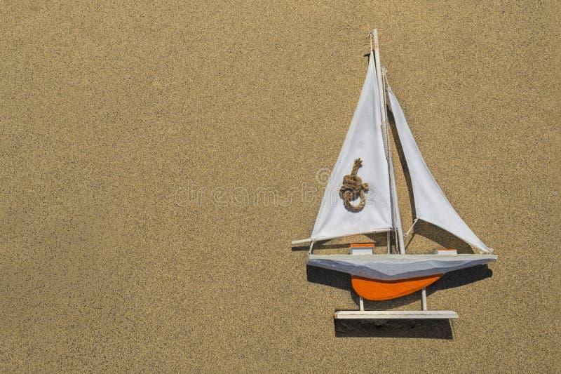 Un bateau orange de jouet avec une voile blanche se trouve sur le sable texturis? du c?t? droit photo stock