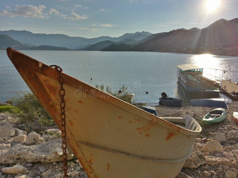 Un bateau rouillé près de lac image libre de droits