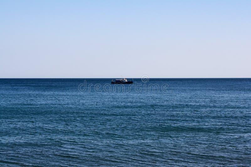 Un bateau solitaire sur l'horizon de mer images libres de droits