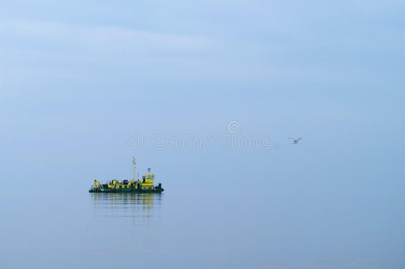 Un bateau solitaire traversant la mer baltique calme photos stock