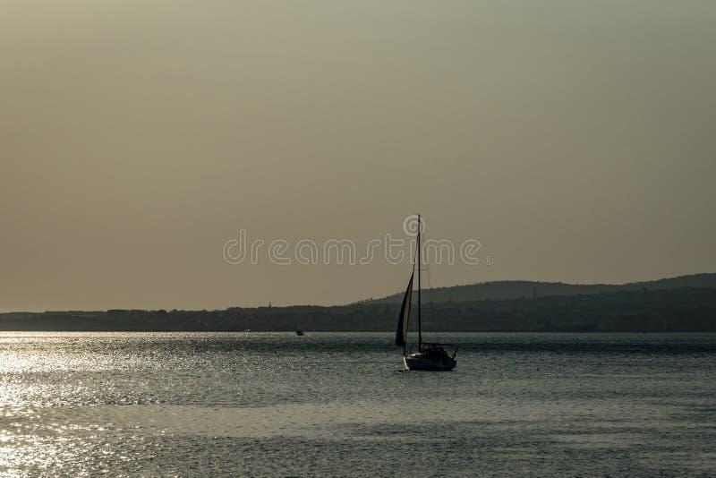 Un bateau sur un fond d'une Mer Noire calme argentée au coucher du soleil Le chemin ensoleillé sur l'eau rend le paysage paisible photographie stock