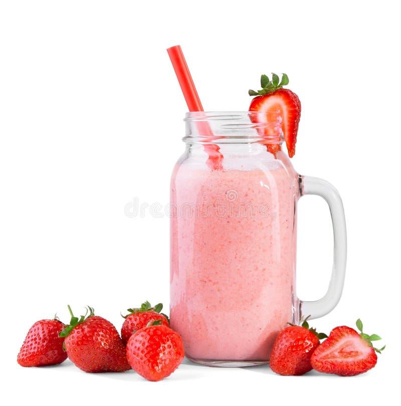Un batido de leche de la fresa en un tarro de albañil Yogur de buen gusto en un fondo blanco Un postre delicioso con una paja roj fotos de archivo libres de regalías