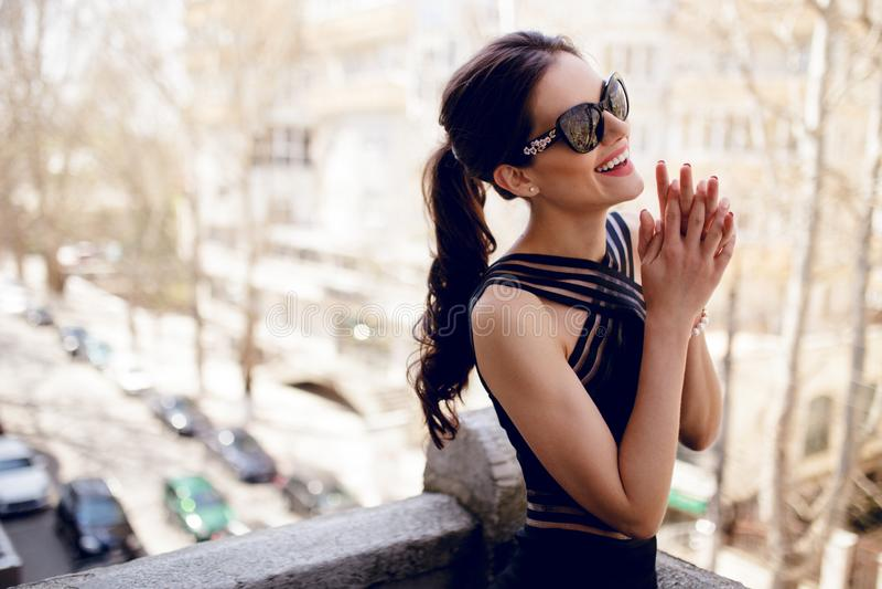 Un beau, brune dans des lunettes de soleil noires et robe, queue de cheval de cheveux, smilling, posant sur le balcon photos stock