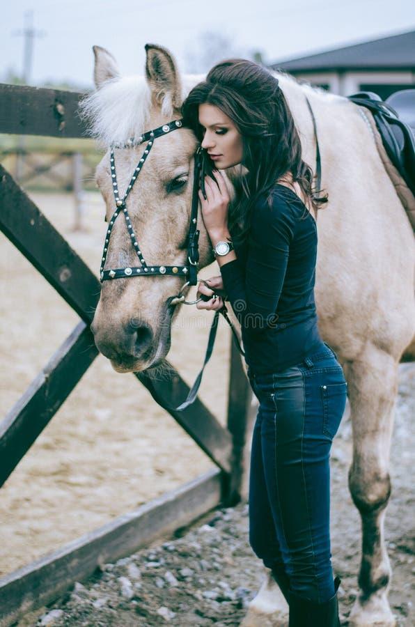 Un beau cavalier de femme parle à son cheval après la monte dans un ranch de pays Photo de mode de vie Photo de mode image libre de droits