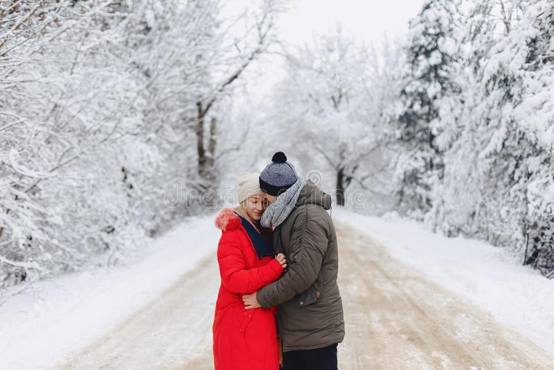 Un beau couple de famille marchant sur une route neigeuse dans les bois photographie stock libre de droits
