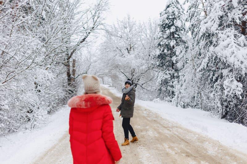 Un beau couple de famille marchant sur une route neigeuse dans les bois images stock