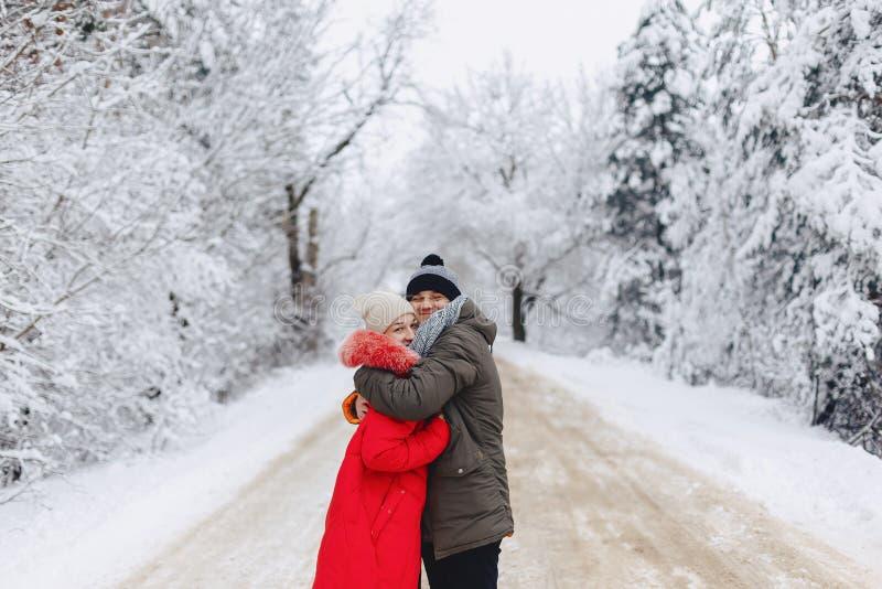 Un beau couple de famille marchant sur une route neigeuse dans les bois images libres de droits