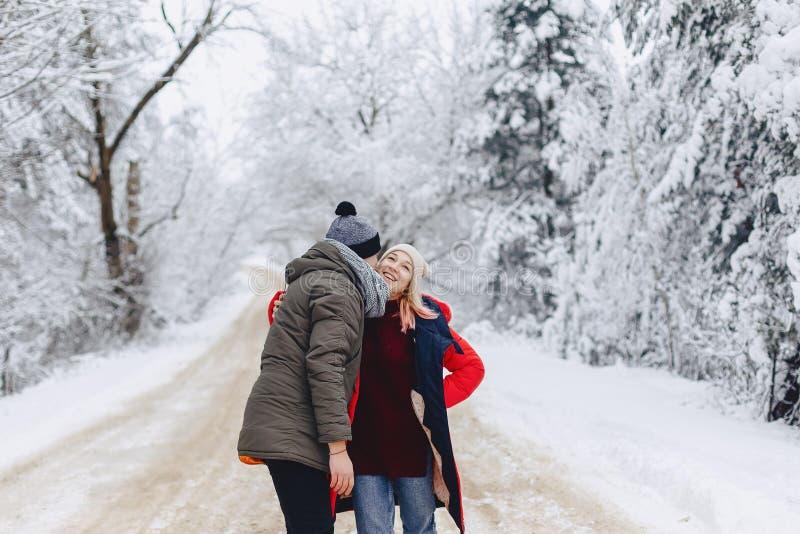 Un beau couple de famille marchant sur une route neigeuse dans les bois photos stock
