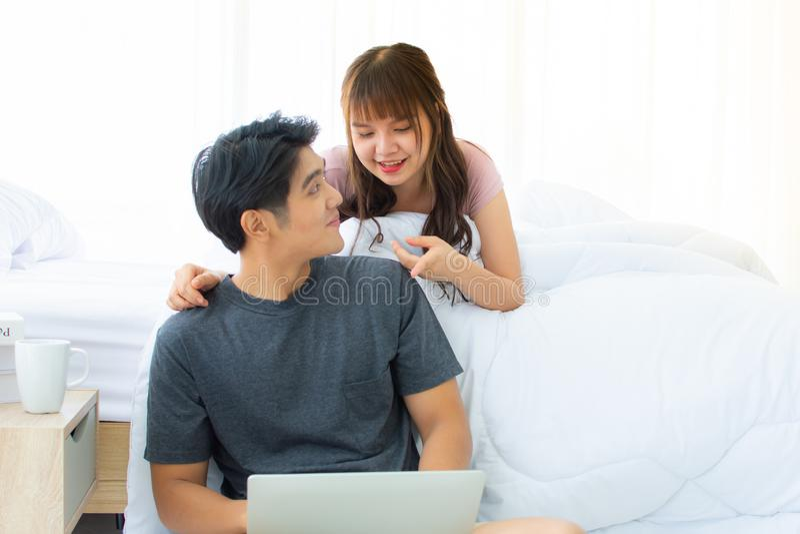 Un beau couple utilise l'ordinateur portable dans la chambre à coucher images libres de droits