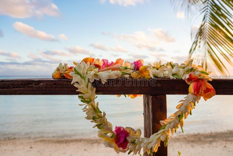 Un beau lei de fleurs repose sur une balustrade en bois surplombant un lagon en Polynésie française dans le Pacifique Sud images stock